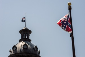 COLUMBIA, SC - JUNE 18:  The South Carolina and American flags fly at half mast as the Confederate flag unfurls below at the Confederate Monument June 18, 2015 in Columbia, South Carolina. Legislators gathered Thursday morning to honor their co-worker Clementa Pinckney and the eight others killed yesterday at Emanuel AME Church in Charleston, South Carolina. (Photo by Sean Rayford/Getty Images)