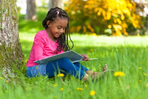 Cute young black little girl reading a book