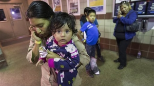 Judy Elizabeth Martinez, holding Marjorie, tries to reach family after being released by ICE at a Greyhound Bus station in Phoenix May 28, 2014. She is from Guatemala and was flown from Georgia to Arizona by ICE. The Border Patrol says about 400 migrants were flown from Texas to Arizona because of a surge in migrants being apprehended in Texas. (AP Photo/