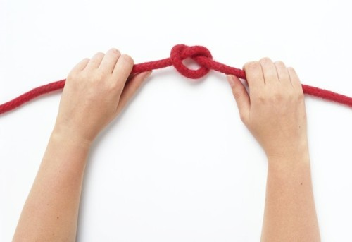 Hands pulling at both ends of a rope to secure a half-hitch knot (Dorling Kindersley photo)