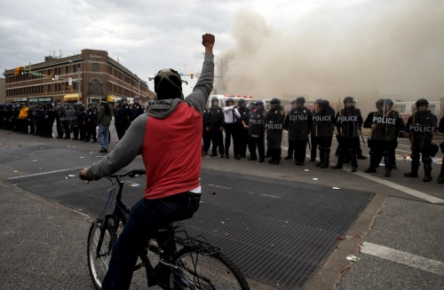A protestor on a bicycle thrusts his fist in the air next to a line of police, in front of a burning CVS drug store, during clashes in Baltimore
